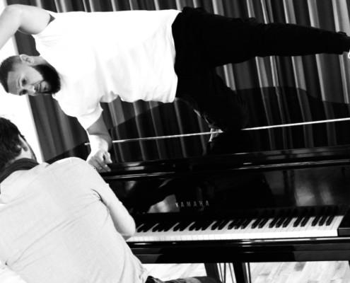 Un homme danse sur un piano