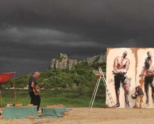 Un homme de la guitare tandis qu'un autre peint