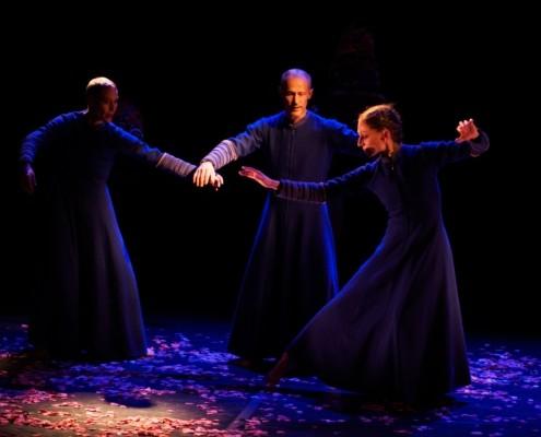 Trois hommes en costumes bleus dansent